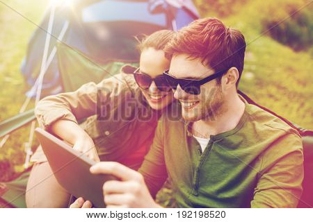 travel, hiking, technology, tourism and people concept - smiling couple with tablet pc computer sitting on chairs at camping tent