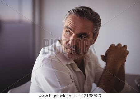Close up of thoughtful mature businessman sitting in office