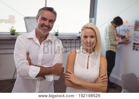Portrait of smiling businessman and businesswoman standing in creative office