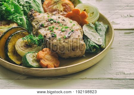 Chicken breast barbecue on wood plate served with grilled vegetables. Delicious chicken barbecue and grilled vegetables for lunch or dinner. Roast chicken breast on wood table. Chicken steak or pork chop with extremely underexposed concept.