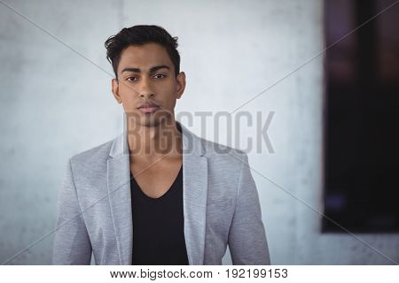 Portrait of young businessman standing against wall at office