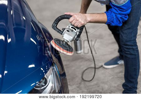 professional mechanic using a power buffer machine for cleaning the body of a car from scratches. Detail of car care concept. The blue car in the garage. A man in a blue uniform