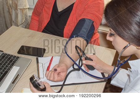 Doctor checking blood pressure of a patient he is measuring heart pulses with a sphygmomanometer healthcare and diagnostics concept