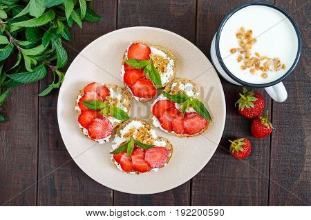 Mini sandwiches with cottage cheese fresh strawberries decorated with mint leaves on rye bread and a mug of yogurt on a dark wooden background. Top view. Proper nutrition. Healthy food. Dietary menu