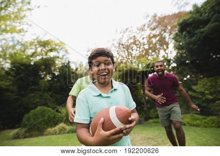 Portrait of boy playing rugby with father and grandfather at park poster