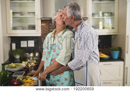 Loving senior couple kissing while cooking in kitchen at home