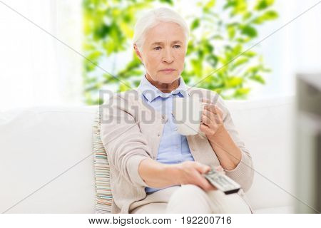 television, age and people concept - senior woman watching tv, drinking tea and changing channels by remote control at home over green natural background