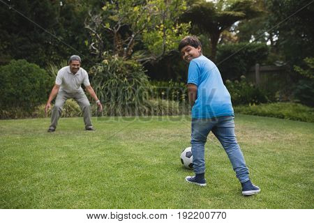 Happy boy playing soccer with grandfather on field at park