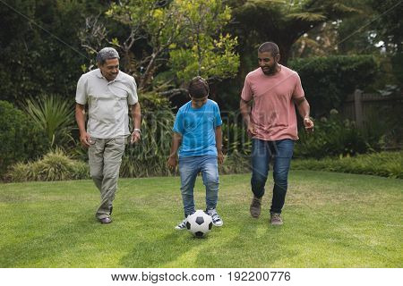 Happy multi-generation family playing soccer together on field at park
