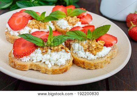 Mini sandwiches with cottage cheese fresh strawberries decorated with mint leaves on rye bread on a dark wooden background. Proper nutrition. Healthy food. Dietary menu