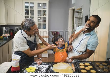 Boy playing with father and grandfather while preparing food together in kitchen at home