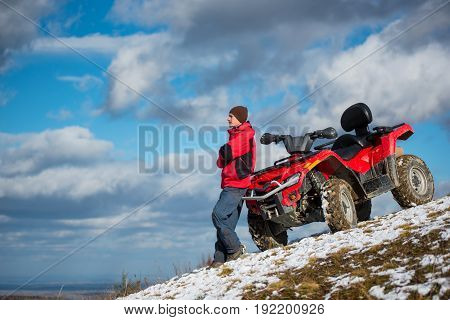Guy In A Red Winter Clothes Standing Near Red Atv Quad Bike, Looking Into The Distance On Snowy Moun