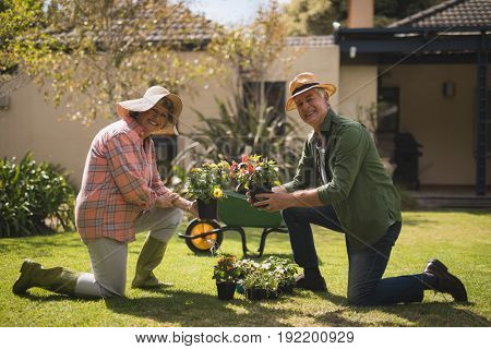 Portrait of smiling senior couple holding plants while kneeling on field in yard