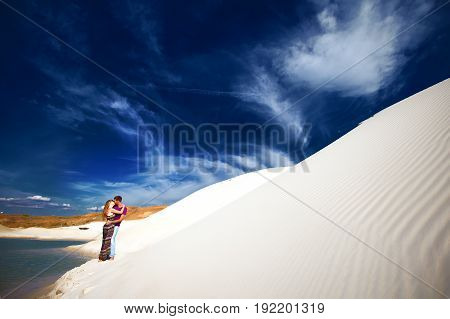 happy couple on romantic travel honeymoon vacation summer holidays romance. Young happy couple on the beach with white sand, caucasian woman and man hugging and kissing