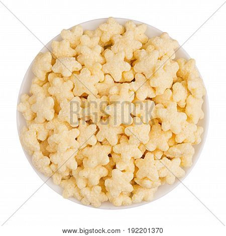 Yellow star corn flakes in white bowl isolated top view.