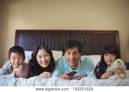 Happy family watching television in the bed room at home