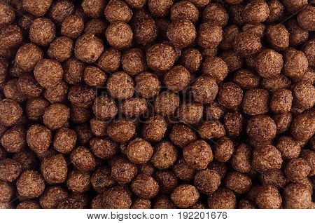 Chocolate balls corn flakes closeup background. Cereals texture. Top view.