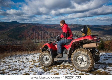 Atv Quad Bike With Driver At The Snowy Slope Against The Blue Cloudy Sky, Mountains And The Town In