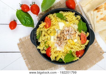 Fusilli pasta fried eggs and tomatoes. Serve on a cast-iron frying pan on a white wooden background. Top view.