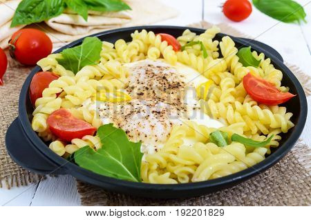 Fusilli pasta fried eggs and tomatoes. Serve on a cast-iron frying pan on a white wooden background.