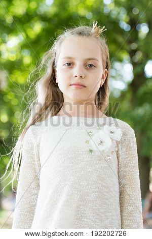 Portrait of a lovely little happy princess girl with long blonde curly hair at summer sunny day