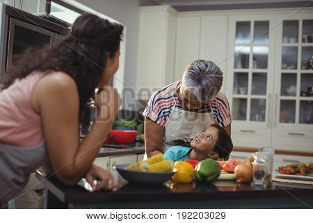 Smiling family interacting with each other in kitchen at home