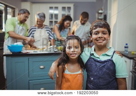 Siblings smiling at camera while family members preparing dessert in background at home