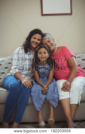 Portrait of happy family sitting on sofa in living room at home