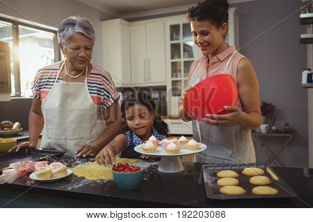 Happy family preparing desserts in kitchen at home