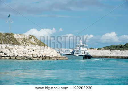 Great stirrup cay Bahamas - January 8 2016: passenger cruise ship or craft in sea or ocean leaving bay with rocky coast on sunny day on blue sky. Water transport. Summer vacation. Traveling