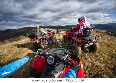 View From Atv A Group Of People Riding A Quad Bikes On A Mountain Road Under A Sky With Clouds In Au