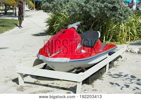 water craft scooter or jet ski boat red color motor vessel parked on ground on sunny day on natural background. Summer vacation. Recreation and sport. Active lifestyle