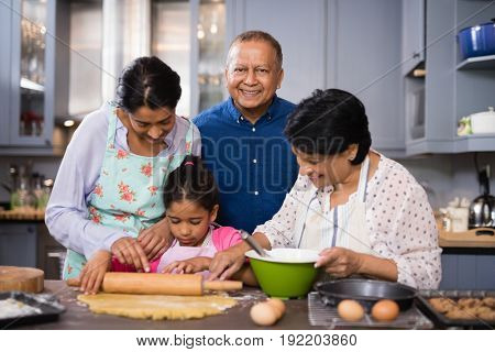 Portrait of smiling mature man standing with family preparing food in kitchen at home