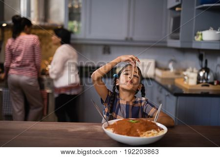 Girl eating spaghetti in kitchen at home