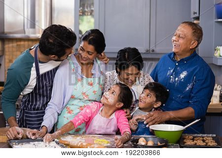 Happy multi-generation family enjoying while preparing food in kitchen at home