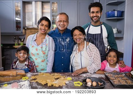 Portrait of smiling multi-generation family standing together in kitchen at home
