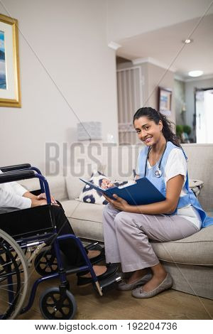 Portrait of smiling young doctor checking patient medical report at home
