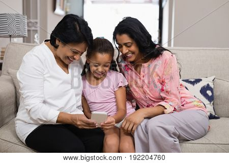 Happy multi-generation family using mobile phone together while sitting on sofa at home