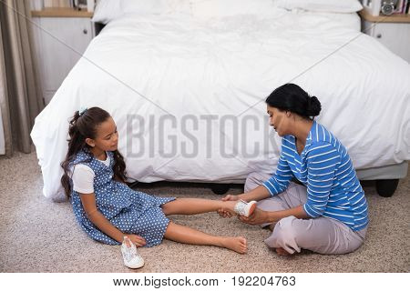 High angle view of mother helping daughter to wear shoe at home