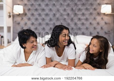 Cheerful multi-generation family lying on bed at home
