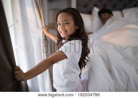 Portrait of of happy girl holding curtains in bedroom at home