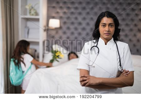 Portrait of serious nurse standing with patient on bed at home