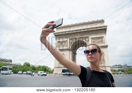 young woman visit paris and making selfie in front of Triumphal arch