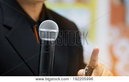 blurred of businessman speech talking with microphone and keynote presentation