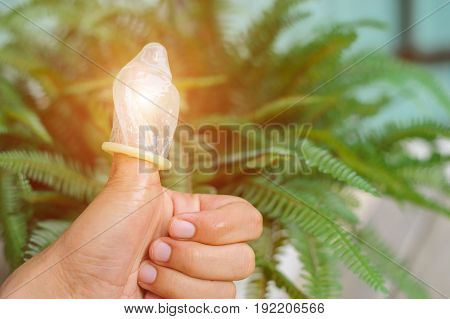 Thumb and condom over a green leaves background , Condom