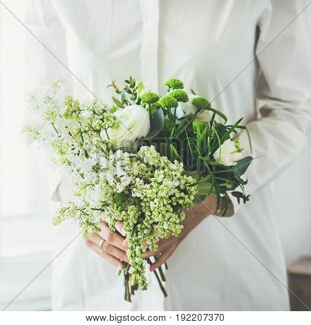Young woman wearing white clothes holding white flowers bouquet composed of ranunculus and lilacs in her hands beside window, square crop. Wedding, flower shop concept