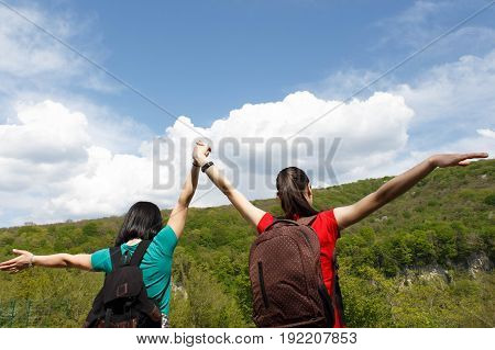 Young hiker girls with backpack enjoying and looking to the sky with clouds. Active hikers