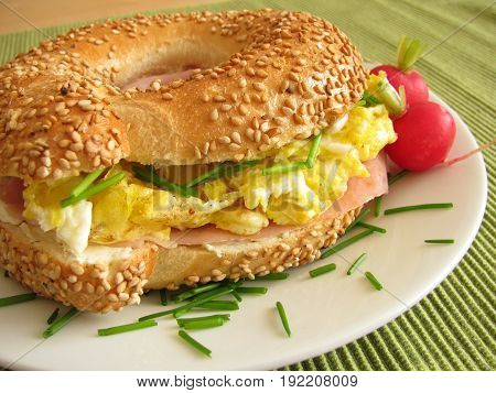 Bagel sandwich with ham and scrambled eggs