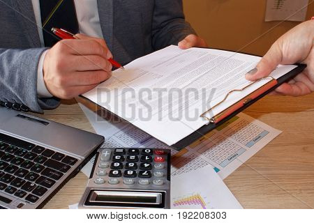 Close up of male hand putting signature in contract businessman signing document. Successful negotiation concept agreeing to terms bound by contract intend to enter in agreement feeling confident