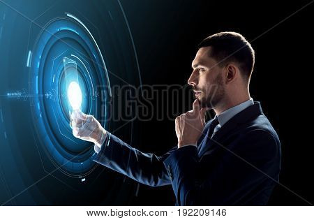 business, augmented reality and future technology concept - businessman in suit working with transparent tablet pc computer and hologram over black background